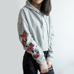 21e945a75c Cropped hoodie with embroidered roses running down both sleeves in a cozy  and fuzzy material.