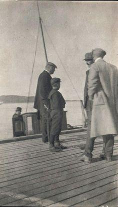 """Troms fylke Harstad """"passiar"""" på bryggekanten i Juli 1911. Nærmest et fotografi, men """"tykk""""kartong. Påskrevet navnet på de 3-4 herrer som prater. Bl a Meierimester Nordmo og statskonsulent Nøkleby"""