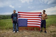 Photo Taken by: Aaron Huey  Pine Ridge Indian Reservation, South Dakota  This photo depicts two Oglala men holding the American flag upside down in order to symbolize defiance against the U.S. government.  The site of this photograph is significant because it is the site of the Wounded Knee Massacre.  This photo is important because it sheds light on the hardships and opinions of Native Americans, people that the news often does not focus on.
