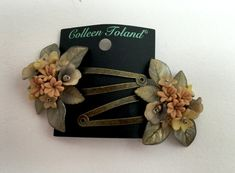 A pair of hand beaded flower snap clips. The flowers and leaves come in tones of taupe and gold with hints of yellow. The flowers are polymer clay and resin flowers and leaves that are hand painted. The clip itself is a simple snap clip with an antique gold finish. Pretty for all