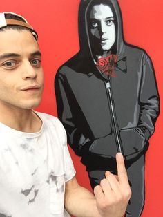 rami malek posing next to art of him as elliot in mr. robot.
