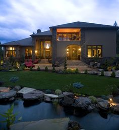 This home has beautiful landscaping complete with a custom pond, uplighting and rocks. The house has stucco and stone siding. Click to see how much it costs to hire a landscaping professional.