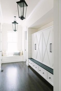 Two seeded glass lanterns illuminate a long mudroom equipped with x-front closed locker doors adorning bronze pulls and fitted in a nook against a wood trim above a white storage bench topped with a dark stained wood seat.