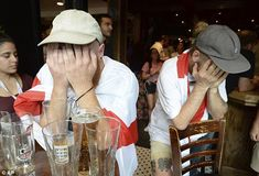 Two England supporters bury their head in their hands after watching their side lose