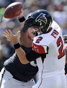 Oakland Raiders defensive tackle Stacy McGee, rear, sacks Atlanta Falcons quarterback Matt Ryan (2) during the first half of an NFL football game in Oakland, Calif., Sunday, Sept. 18, 2016.
