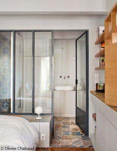 salle de d'eau dans suite parentale avec un style vintage  une verrière en séparation soutenu avec une délimitation du sol par le changement  du parquet aux carreaux de béton