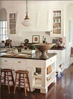 White kitchen with black granite counter and large island ~ schoolhouse pendant ~ glass  upper cabinets ~ Country Home magazine