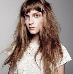 Ragazza con i capelli castani con frangia e un look naturale spettinato