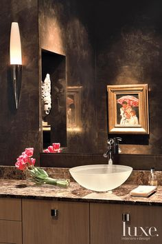 Chocolate-hued plaster on the walls and dark marble countertops envelop this Dallas powder room. See more at www.luxesource.com.