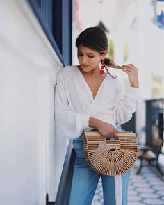 red pompom earrings, white shirt, denim & the cult gaia ark bag