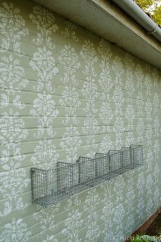 Image of exterior garage wall painted sage green with a stencilled damask design in white