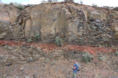 Maybe weathering is the key: So the story recorded here could therefore be: lava erupts, lava cools to basalt, basalt weathers from the top down, producing clay and rust-rich saprolite, new lava erupts, cooks weathered basalt beneath, baking it orange.