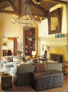 Remove the trunk and place a beautiful console behind the sofas with matching lamps!! Add side tables, style bookcase and dress up the mantle.(Michael Smith)