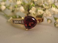 Trillion cut red garnet & diamond ring in 10k yellow gold. This one is so classy and pretty and would look great on you or your loved ones finger! The trillion cut looks great with this red garnet. A fantastic price at $127.50