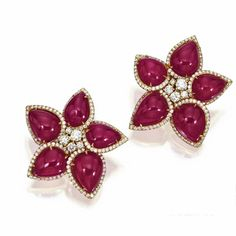 PAIR OF RUBY AND DIAMOND EARCLIPS Designed as flowerheads set in the center with round diamonds, the petals set with 10 pear-shaped cabochon rubies weighing approximately 78.00 carats, within frames of small round diamonds, the total diamond weight approximately 2.55 carats, mounted in 18 karat gold.