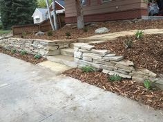 Stacked Sandstone retaining wall with stone steps and walkway. Stone walkway winds itself through the front yard. Chuck at CW Designs designed and installed this for us. .