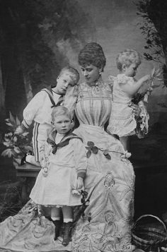 Photograph of Queen Mary (1867-1953) when Duchess of York and her two eldest sons Prince Edward (later King Edward VIII) (1894-1972) and Prince Albert (later King George VI) (1895-1952), dressed in sailors' suits and Princess Mary (1897-1965), playing with flowers