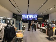 Screens showing product and lifestyle images are displayed at the back of the store.