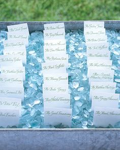 White escort cards with calligraphy rest atop a bed of smooth-edged blue sea glass that keep cards anchored.