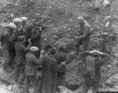 A US soldier holds a group of German troops and laborers at gunpoint in a ditch during World War II, Omaha Beach, Normandy, France, on June 6, 1944. (Hulton Archive/Getty Images)