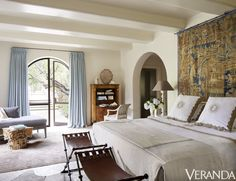 A bedroom that opens into the garden in this Santa Barbara home has bedding by Julia B., stools by Formations and a chaise in a Great Plains cotton velvet.