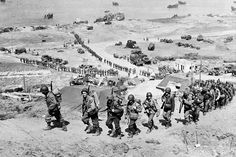 June 18, 1944: US Army reinforcements march up a hill past a German bunker overlooking Omaha Beach after the D-Day landings near Colleville sur Mer, France
