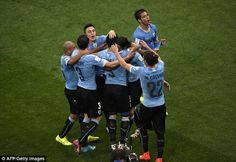 Star man: The Uruguay players congratulate the forward, who had just returned from injury...