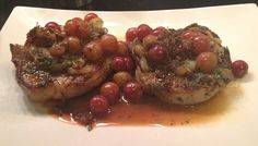 Dijon porks chops with herbs and grapes on a platter.