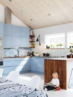 Kuchnia z niebieskimi meblami i industrialną lampą biurową