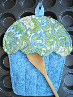 This beautiful paisley blue and white fabric looks so elegant! The cupcake oven mitt measures 8 across and 9 tall plus 2 for the ribbon hanger. Ive used 100% cotton quilt shop quality fabric on the front and back and under the icing. Inside the cake is two layers of insulation to protect you from burns - one layer of cotton batting and one layer of insul-bright. Ive used cotton batting inside the icing as well. There are 3 rows of quilting stitches on the base and top stitching all around…