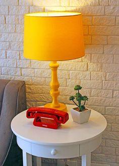 Parede de tijolinhos brancos, telefone moderno-retrô e luminária laranja compõem o cantinho aconchegante da sala