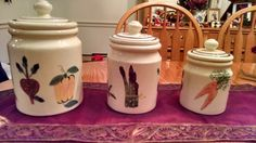 "Vintage Beautiful Hartstone ""Farmer's Market"" ceramic handpainted 3 piece canister set.  Excellent used condition. No chips, No cracks, No crazing.  Off white base color with hunter green and maroon stripes on lids.  The colors of veggies Purple, orange, yellow, green, brown and white are bright and the pottery is shiny and clean.  Buy it now on ebay for $75 OBO."