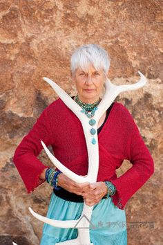 Portrait of a strong and fierce senior woman holding an elk antler. Jewelry by Art Medicine Adornment.