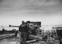 A Coast Guardsmen checks out German artillery on Omaha beach