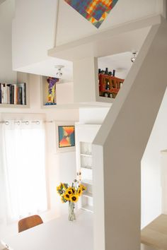 Floating shelves made of painted birch plywood fold and dip all around this loft room, providing spots for books and art.