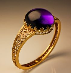A Victorian 19th Century Gothic Style Amethyst and Gold Bangle Bracelet.  circa 1850. A14K gold openwork hinged bracelet features a huge round cabochon cut amethyst (27.5 x 13.1 mm, approximately 70 carats)  set in a crown like gold bezel.  The bracelet is decorated with an elaborate gold strapwork in medieval Gothic style. The amethyst is detachable and can be worn as a slide pendant.
