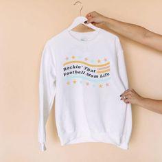 Rocking That Football Mom Life Sweatshirt - The Stadium Chic. Sweatshirt, pullover, hoodie, football mom, mom, women, feminine, football, American football, T-shirt, tee, graphic tee, football mom, gift, NFL, trendy, chic. Football Outfits, American Football, Hoodies, Sweatshirts, What To Wear, Nfl, Graphic Tees, Feminine, Unisex