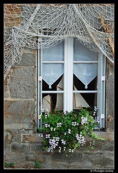 Voiles et voilages. Filet de pêche, et maquettes de vieux voiliers derrière cette fenêtre très vieille marine.