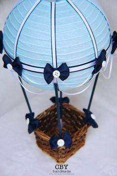 Este centro de mesa globo aerostático maravillosamente hecha a mano se hace uso de una linterna de papel azul claro que ha sido adornada con cintas de azul marino y blanco de alta calidad. Está adornado con cinta blanca y azul marina drapeado y adornado con arcos de la marina de guerra