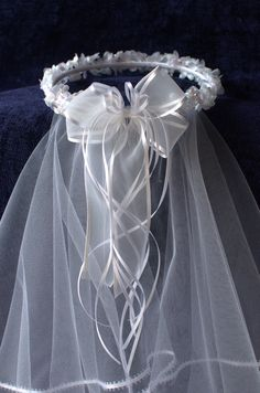 Beautiful Handmade First Communion or Flower girl Veil. White iridescent flowers adorn the crown. A white sheer bow adorns the back of the crown with thin white curled ribbon hanging down. The crown has a clear comb attached to secure the veil in place. The veil is made of white tulle with white trim. A beautiful head piece for their special day! *I also do custom orders. If you see anything in my shop that you would like to customize, dont hesitate to message me. I can add more or less…