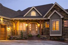 I like the style of this home with the combination of stone and siding, wood carriage garage doors and wood supports on the porch.