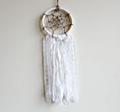 Small White Dreamcatcher Measures 4 (10 cm) across hoop by 13 (33 cm) in length (not including twine hanger)    The center is handwoven with jute