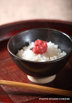 Bed of plain white rice with a single umeboshi in the middle, resembling the Japanese flag