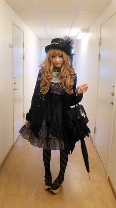 Elegant, classic lolita: Black hat. Black coat. Black handbag. Purple/gray, pleated dresswith white bow. Black and gray tights. Necklace. Black shoes.