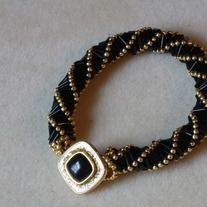 Black+bugle+and+gold+seed+beads+combined+with+the+Russian+Spiral+stitch+makes+this+beautiful+bracelet. The+clasp+is+made+with+a+gold+and+black+button.