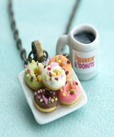 This necklace features a miniature plate of handmade donuts sculpted from polymer clay along with a miniature Dunkin donut coffee cup charm. the miniature cup and the ceramic donut plate charm are att