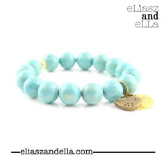 - stretchable, stackable light blue river stone (12mm beads) bracelet - antiqued brass baby bird charm + Eliasz and Ella logo charm