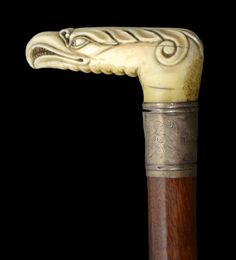 Cane with a carved walrus ivory knop in the form of an eagle's head made all the more ferocious appearing by the spurious addition of numerous teeth.