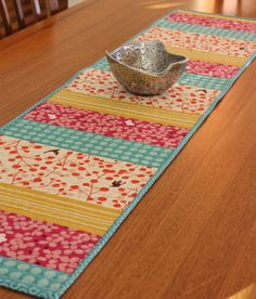 Simple Table runner. Looks like she used a walking foot to make even ridges. Colors are different widths but each piece of the same color is the same width.