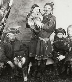 A Nordic Sami or Laplander family in traditional costumes and a dog from Finland. Circa 1936